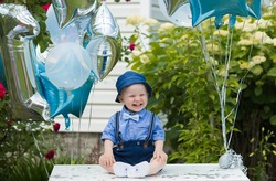 A beautiful little boy kid gentleman in a retro suit with suspenders and a bow tie is sitting on a white tablen. Children's party with balloons happy birthday, 1 year.