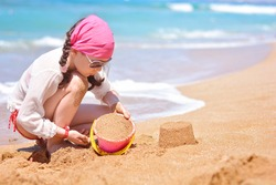 A beautiful little girl builds sand towers on the beach near the sea. Family beach leisure and vacation concept