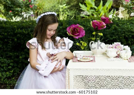 A beautiful little girl having an outdoor tea party with her baby doll