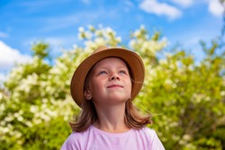 A beautiful little girl in a hat looks at the sky. A child in a blooming garden.