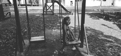A beautiful little girl sits on a swing and looks at the camera. Child 6 years old in a dress on the playground. Monochrome image. Retro style. Black and white photography
