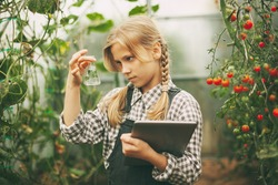 A beautiful little teenage girl with a tablet in her hands examines a sample of a plant through a magnifying glass. Curious children. Organic pure products