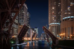 A beautiful long exposure photograph looking down the Chicago River at night as loop bridges along Wacker Drive in downtown are raised up in effort to curb violence and looting and restrict access.