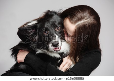 A beautiful long-haired girl tightly hugs her dog breeds a border collie, she hides her face in wool. #615608885