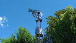 a beautiful low angle shot of a traditional rural windmill in for pumping water in a farm in Buenos Aires, Argentina  Copyspace