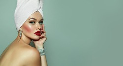 A beautiful, luxurious young girl with green eyes and bright make-up sits after the bathroom with a white towel on her head and in shining decorations. Earring t bracelet.