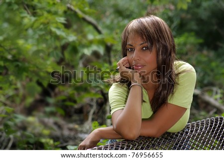 A beautiful mature black woman soaks up some atmosphere on a park bench amidst lush tropical vegetation outdoors, looking directly into the camera.