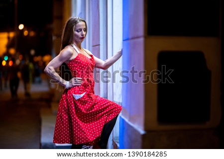 A beautiful mature woman in a red dress checking the storefront at night with the city lights in the background.