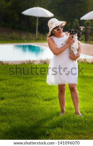 a beautiful mature woman playing with a little dog in a vibrant meadow