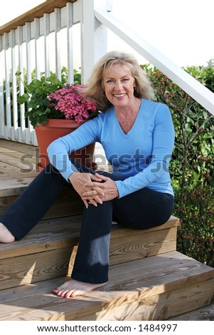 A beautiful, mature woman relaxing at home on her front porch.