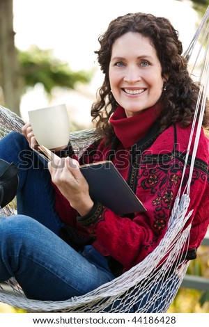 A beautiful mature woman sitting on a hammock reading a book - stock photo