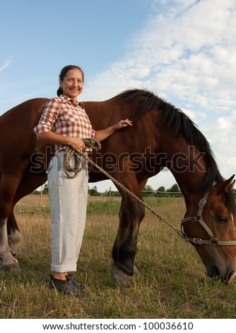 A beautiful mature woman stands next to horse with a happy smile on her face