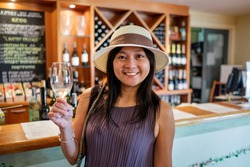 A beautiful matured chinese asian lady wine tasting and feeling happy.