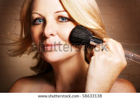 A beautiful middle aged woman applying blusher and looking at the camera.