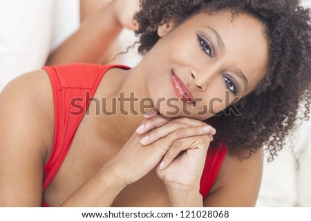 A beautiful mixed race African American girl or young woman laying down on a sofa wearing a red dress looking happy
