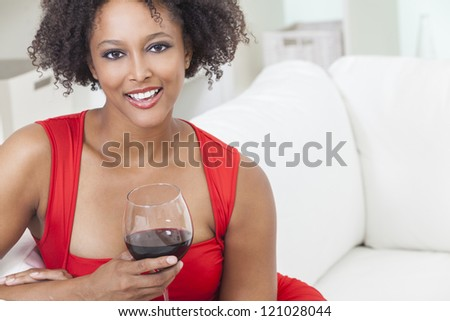 A beautiful mixed race African American girl or young woman wearing a red dress looking happy and drinking red wine - stock photo