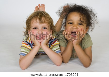 A beautiful mixed race girl and a blonde boy laying next to each other laughing
