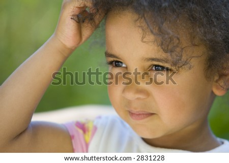 A beautiful mixed race girl lit by summer sunshine, scratching her head and thinking