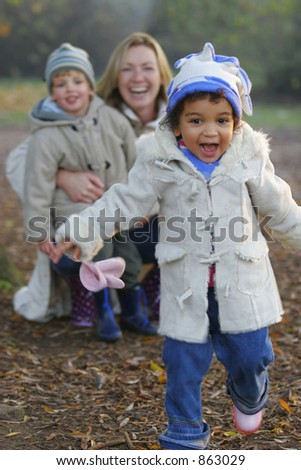 A beautiful mixed race girl runs towards the camera laughing while over her shoulder you see a young mother with her son.