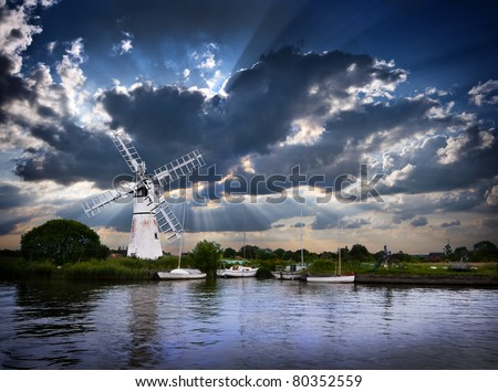 a beautiful moody image of a traditional norfolk windmill or wind pump with four moored sailing boats at early evening with a spectacular sun beam sky beyond