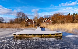 A beautiful morning by a lake with a frozen boat dock and two wooden cottages used for storing boat accessories.