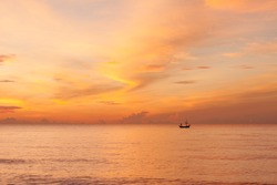 A beautiful morning sky with a fisherman on a boat in the sea, a beautiful orange sky with cloud reflection on the sea. Taken at Hua hin beach, Prachuabkhirikhan, Thailand.