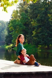 A beautiful mother sits with her son on the edge of the lake bridge, her legs dangling down, with a beautiful landscape of nature.