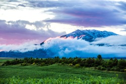 A beautiful mountain peak towering through the low lying clouds tinted in pink from a beautiful summers evening overlooking a farm field in Idaho.