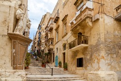 A beautiful narrow lane with typical Maltese architecture. The wall of the building decorated a stone sculpture of saint.