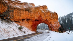 A beautiful natural red rock arch tunnel in the middle of a small highway in southern Utah on a cold winter snow day.