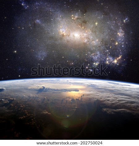 A beautiful nebula (the irregular galaxy, NGC 4449) over the Earth. Elements of this image furnished by NASA.