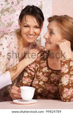 A beautiful nice older woman with her adult daughter on a pink background