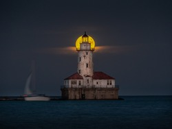 A beautiful night shot of the harvest full moon as it aligns with the center top of the abandoned historic light house tower along Lake Michigan in Chicago as sailboat passes by on the dark water.