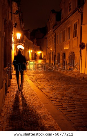 a beautiful night view of the street and the shadow of a man in Prague