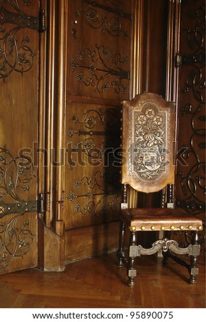 A beautiful old chair and wooden wall in a Royal Chamber in Czocha Castle, Poland