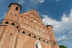 A beautiful old fortress church made of red brick against a blue sky background. A high impregnable fortress with iron crosses on the domes, arched windows and an icon in the center of the wall.