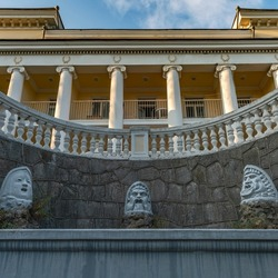 a beautiful old fountain with sculptures of the faces of the ancient gods on the pediment of the building