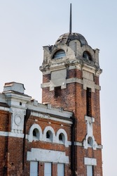 A beautiful old red brick building with a 19th century tower. Abandoned house with beautiful architecture in the city center. Vertical photo.