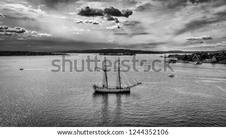 A beautiful old sailing ship lying nearby the harbor of Oslo. In the background the Fjord of Oslo and a very dramatic sky. Taken from the deck of a Cruise ship in August. Black and White picture