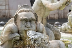 A beautiful old stone fountain of a fish and abstract human head with running water from the mouth. Classical piece of art in the historical center of Rome, Italy