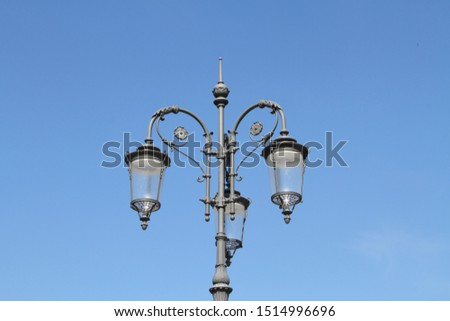 a beautiful old three-lamp street lamp
