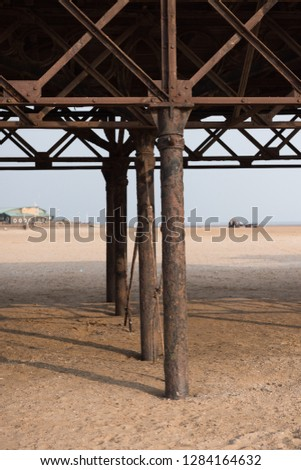 A beautiful old vintage steel iron victorian seaside pier structure shot from beneath, victorian architecture on the sandy beach, seaside landmark buildings. #1284164632