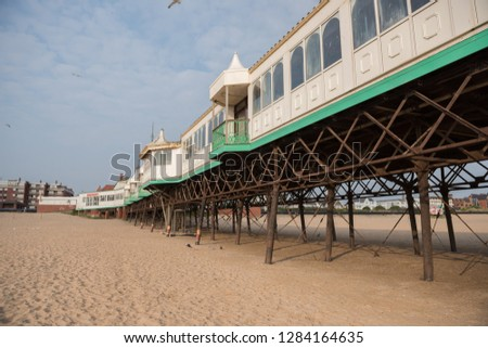 A beautiful old vintage steel iron victorian seaside pier structure shot from beneath, victorian architecture on the sandy beach, seaside landmark buildings. #1284164635