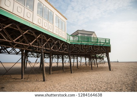 A beautiful old vintage steel iron victorian seaside pier structure shot from beneath, victorian architecture on the sandy beach, seaside landmark buildings. #1284164638