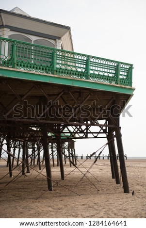 A beautiful old vintage steel iron victorian seaside pier structure shot from beneath, victorian architecture on the sandy beach, seaside landmark buildings. #1284164641