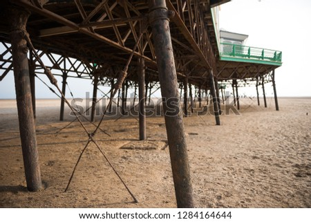 A beautiful old vintage steel iron victorian seaside pier structure shot from beneath, victorian architecture on the sandy beach, seaside landmark buildings. #1284164644