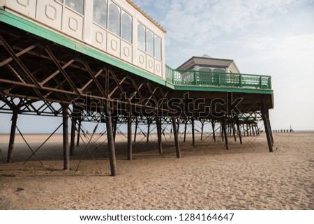 A beautiful old vintage steel iron victorian seaside pier structure shot from beneath, victorian architecture on the sandy beach, seaside landmark buildings. #1284164647