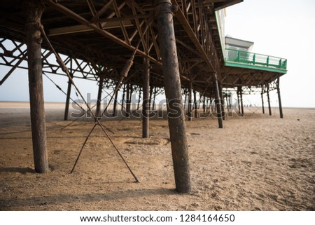 A beautiful old vintage steel iron victorian seaside pier structure shot from beneath, victorian architecture on the sandy beach, seaside landmark buildings. #1284164650