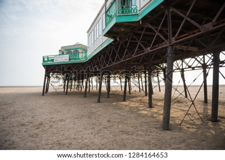 A beautiful old vintage steel iron victorian seaside pier structure shot from beneath, victorian architecture on the sandy beach, seaside landmark buildings. #1284164653