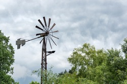 a beautiful old windmill water tower in a field on a beautiful summer day with a cloudless blue sky in and green forest. Zoo Zlin-Lesna, Czech Republic, Europe.